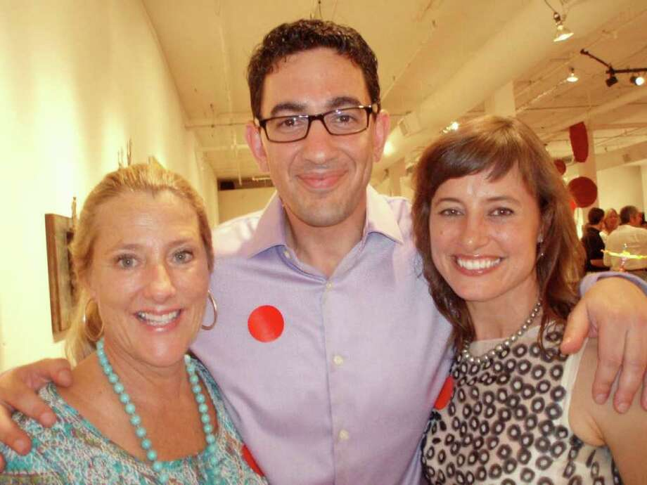 Helen Huff (from left) discusses with Ziad and Jo Sawalha the varied styles of painting styles at the Blue Star Red Dot Art Sale last Thursday.