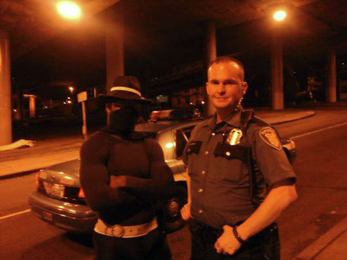 The man who goes by Phoenix Jones Guardian of Seattle with a Seattle police officer in an undated photo.
