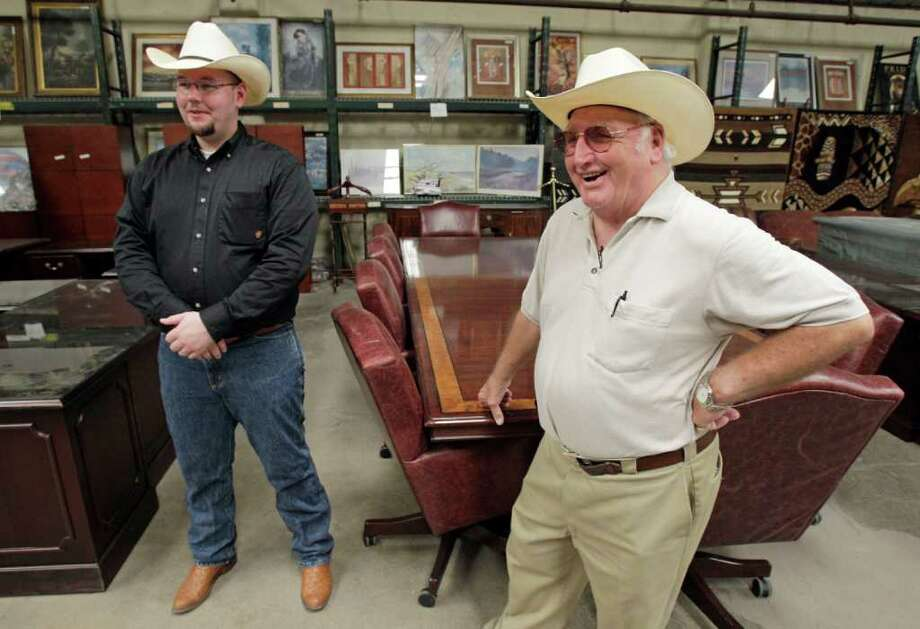 Seth Worstell, left, and Harry Worstell, right, talks near a large conference table, one of many items that belonged to disgraced financier Allan Stanford that will be auctioned at Seth Worstell Auction Company, 4200 Blaffer Street, shown Tuesday, May 31, 2011, in Houston. Other items include a Baccarat crystal eagle statue,  IT equipment, office furniture, china and crystal. Photo: Melissa Phillip, Houston Chronicle / © 2010 Houston Chronicle