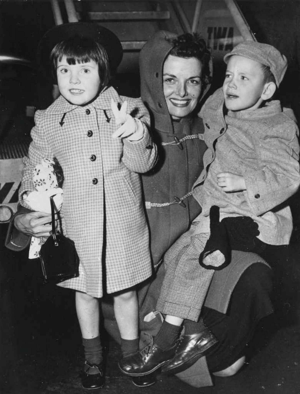Jane Russell meets her two children, Tracy and Tommy, at New York airport after a visit to Europe, circa 1955.