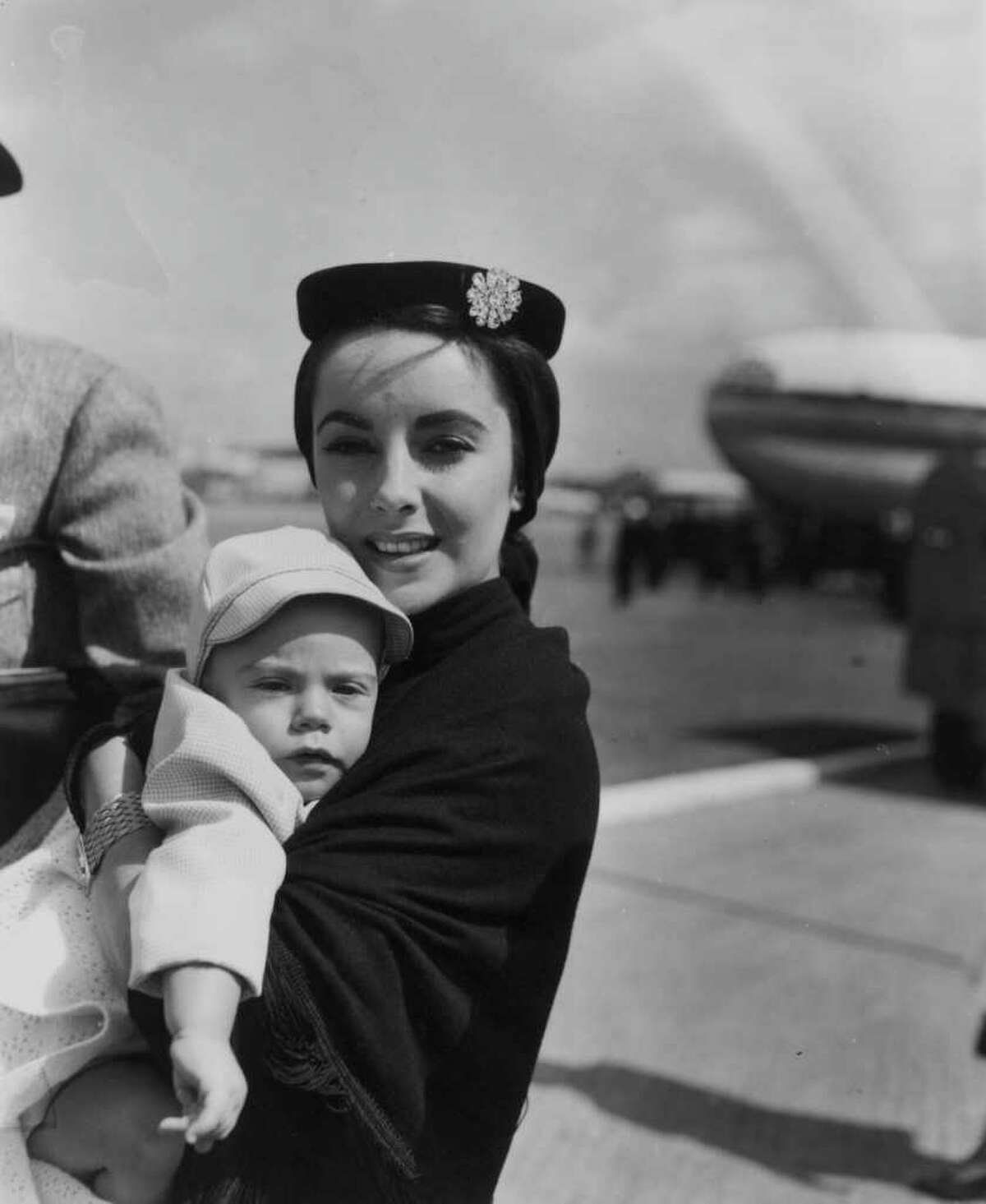 Elizabeth Taylor carries son Michael Howard, aged 7 months, at London Airport, circa 1955.