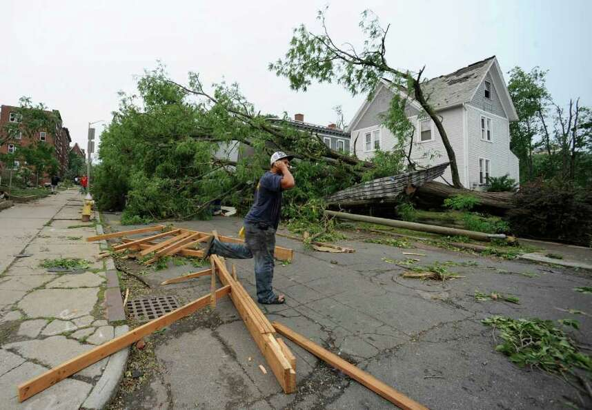 A man talks on his phone near storm damage after a reported tornado struck downtown Springfield, Mas