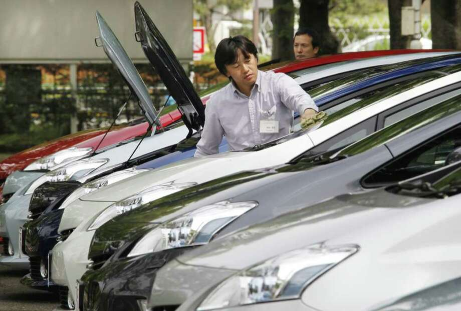 "FILE - In this May 13, 2011 file photo, an employee of Toyota Motor Corp. cleans the ""Prius a,"" or ""Prius alpha,"" a revamp of its popular gas-electric hybrid, during its launch in Tokyo. Toyota Motor Corp. said Wednesday, June 1, 2011, May U.S. car and truck sales fell 33 percent over the same month last year as the automaker was hit by earthquake-related shortages. Photo: AP"