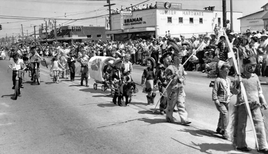 A July 1950 Pioneer Days parade photo looking north in what's now the 12300 block of Lake City Way Northeast. The lumber and hardware company of Dorm Braman, who went on to be mayor of Seattle mayor in the 1960s, is seen on the right, where the Chase Bank and Claire's Parnty is today. Photo: Seattlepi.com File