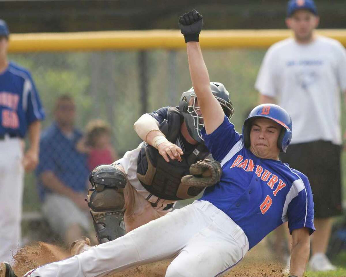 Danbury's B.J. Nimer slides home safely under the high tag of Staples catcher Mike McGowan during the Hatters' 6-4 win in the second round of the Class LL state tournament Wednesday at Danbury High School.