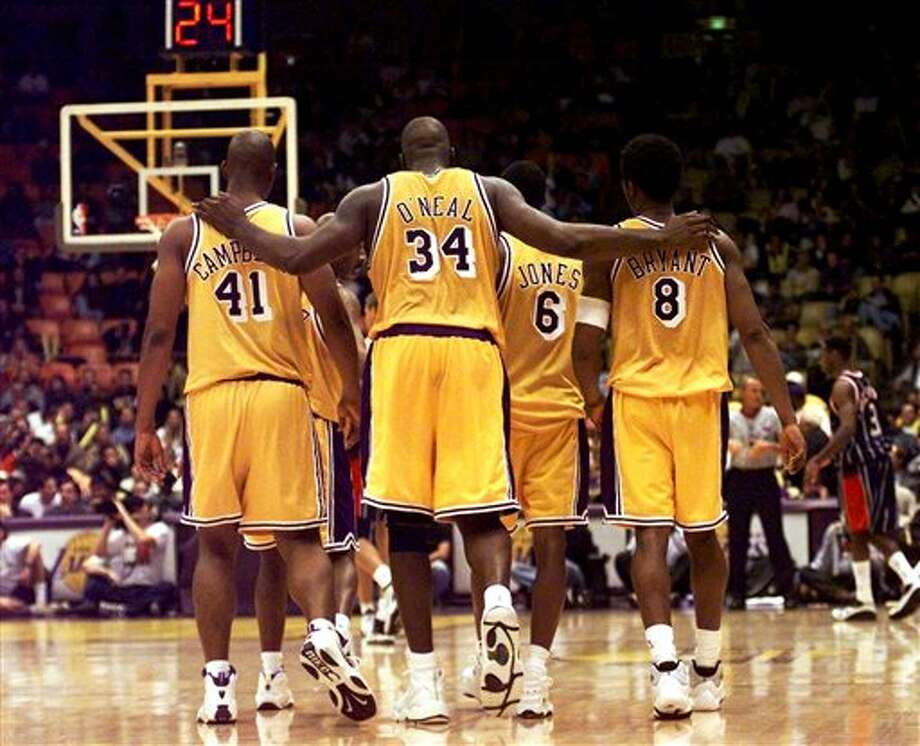 "This Feb. 5, 1999 file photo shows Los Angeles Lakers center Shaquille O'Neal (34) putting his arms around teammates, Elden Campbell (41) and Kobe Bryant (8) as Eddie Jones (6) and Derek Harper walk in front as they return to play the Houston Rockets in the fourth quarter at the Great Western Forum in Inglewood, Calif. O'Neal says on Twitter that he's ""about to retire."" O'Neal sent a Tweet shortly before 2:45 p.m. saying, ""im retiring."" It included a link to a 16-second video in which he says, ""We did it; 19 years, baby. Thank you very much. That's why I'm telling you first: I'm about to retire. Love you. Talk to you soon."" (AP Photo/ Victoria Arocho,File) Photo: Associated Press"
