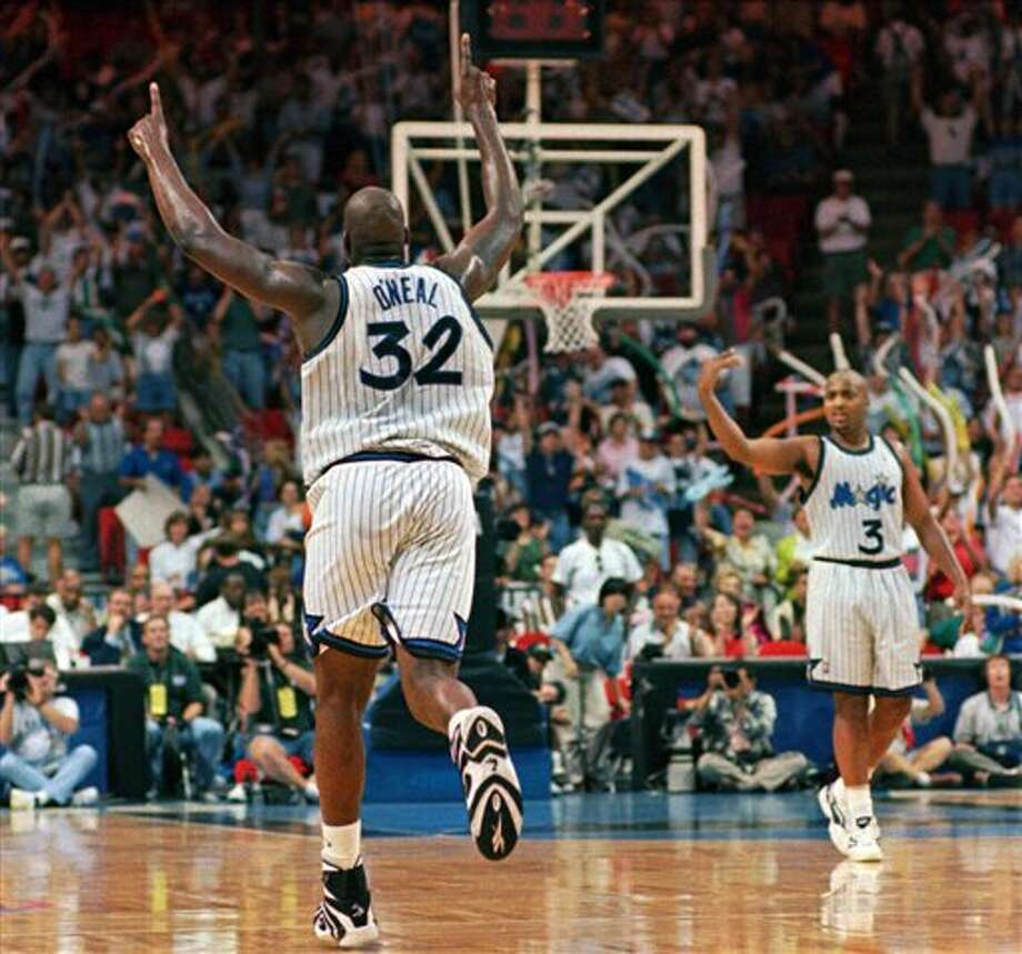 "This April 28, 1996 file photo shows Orlando Magic center Shaquille O'Neal (32) running down the court giving the number one sign after making a slam dunk during the final minutes of the Magic's 92-77 win in game two of the Eastern Conference Quarterfinals against he Detroit Pistons in Orlando.  Helping celebrate is Dennis Scott (3).  O'Neal says on Twitter that he's ""about to retire."" O'Neal sent a Tweet shortly before 2:45 p.m. saying, ""im retiring."" It included a link to a 16-second video in which he says, ""We did it; 19 years, baby. Thank you very much. That's why I'm telling you first: I'm about to retire. Love you. Talk to you soon."" (AP Photo/Chris O'Meara,File) Photo: Associated Press"