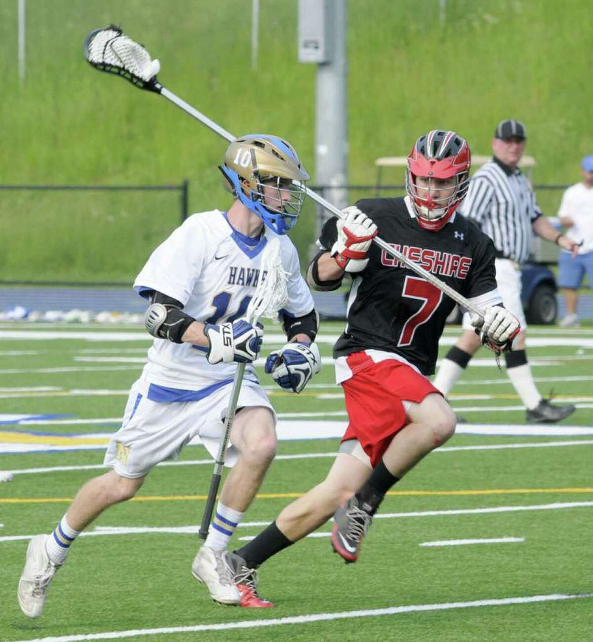 Tim Murphy, left, #10, of Newtown High School, runs up field, against , Nick Palladino, #7, of Cheshire, during a SWC first round Class L boys lacrosse game, against Cheshire High School, at Newtown, on Wednesday, June 1, 2011.