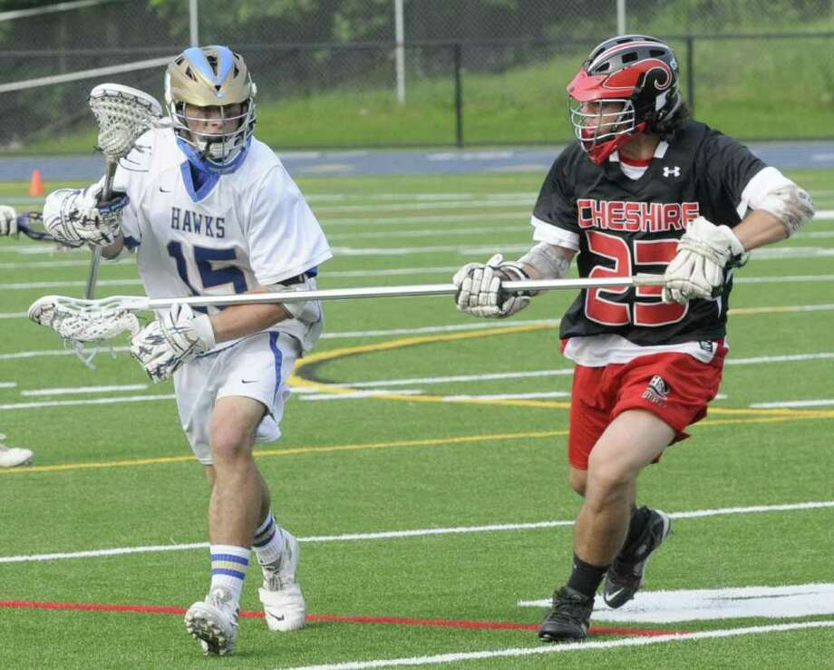 Cory Fisher, #15, of Newtown High School, gets checked by,Torrey Martone, #23, of Cheshire, during a SWC first round Class L boys lacrosse game, against Cheshire High School, at Newtown, on Wednesday, June 1, 2011. Photo: Jay Weir / The News-Times Freelance