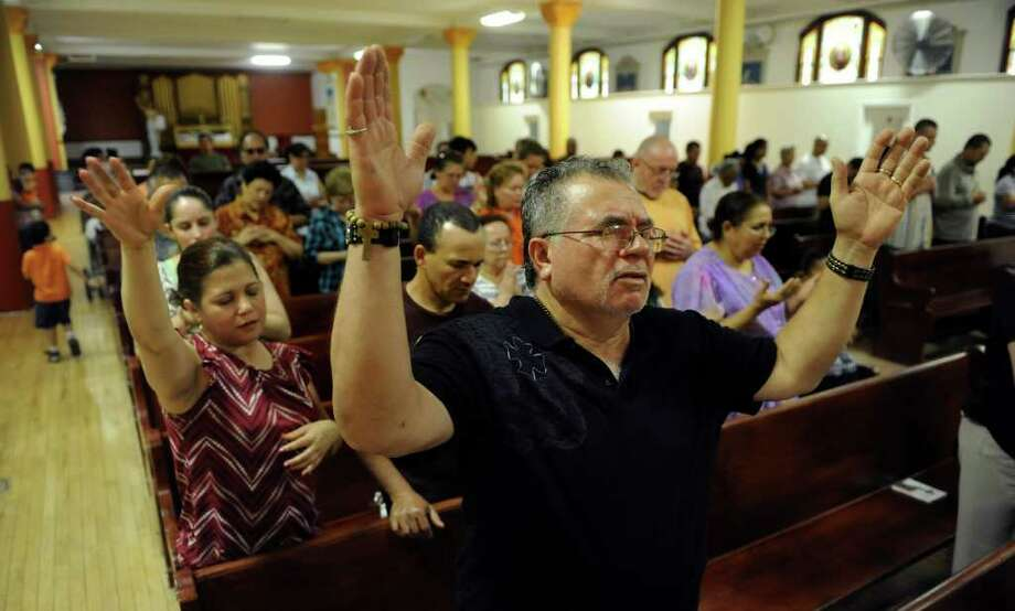 Billy Rodriguez prays with his arms outstretched, during a Spanish service by Father Edicson Orozco at Saint Charles Borromeo Parish on Ogden Street in Bridgeport, Conn. on Wednesday June 1, 2011. Photo: Christian Abraham / Connecticut Post