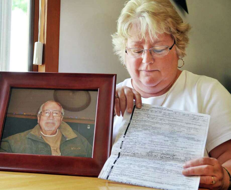 Sue Palmer with a portrait of her late husband Herbert and a copy of his death certificate in the kitchen of her Troy home Friday morning May 27, 2011.  (John Carl D'Annibale / Times Union) Photo: John Carl D'Annibale / 00013320A