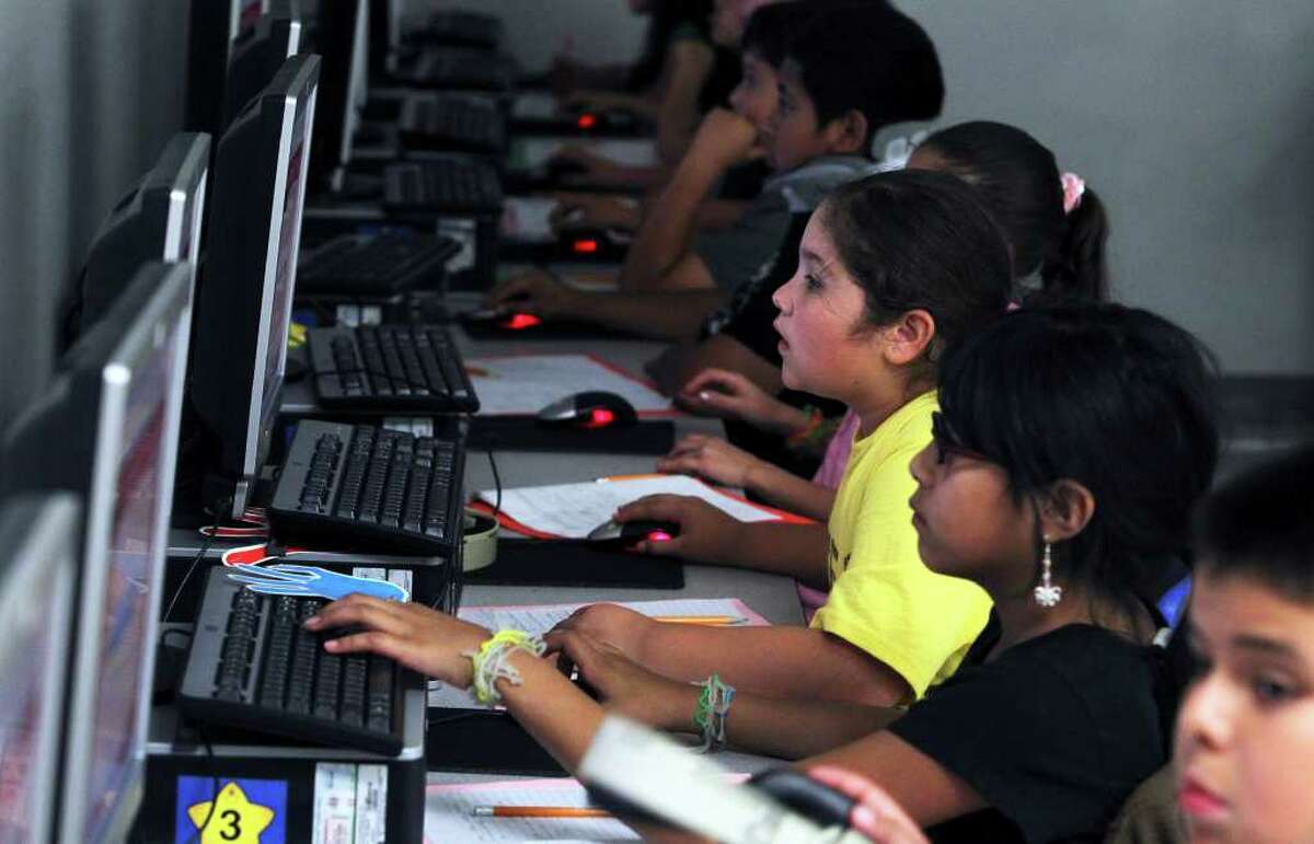 Brianna Centeno (center) concentrates as fourth-grade students at Paschall Elementary work in the computer lab with the Reasoning Mind math program.
