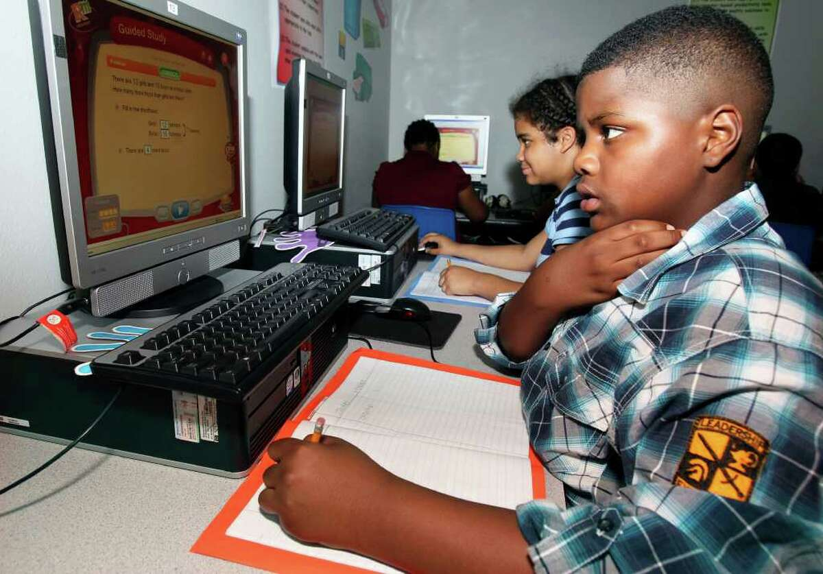 Kenneth Deckard moves through a problem as fourth-grade students at Paschall Elementary work in the computer lab with the Reasoning Mind math program.