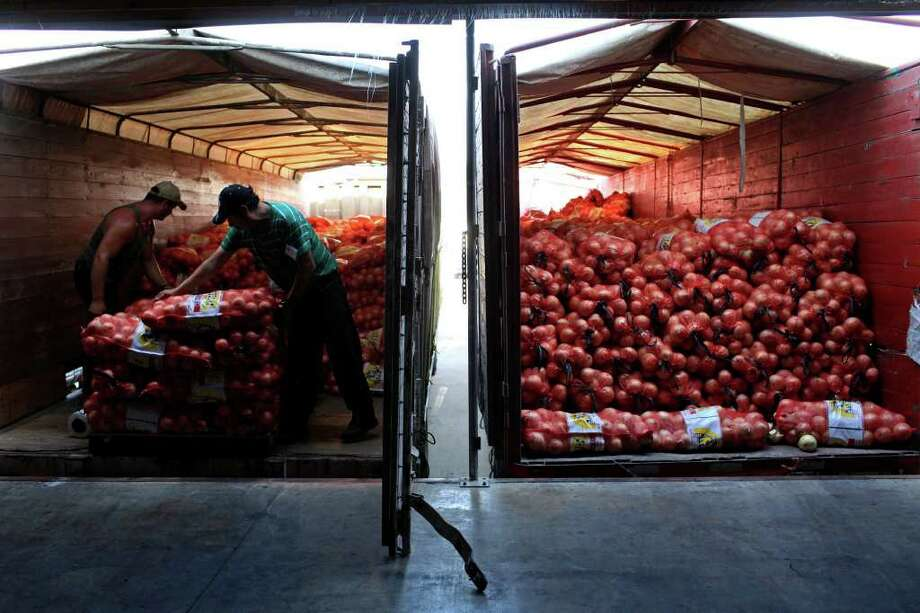 Jesus Valenzuela and Gregorio Avila pack onions from Mexico onto trucks at Progreso Produce in Pharr. Eighty-one percent of 2010 surface trade between the U.S. and Mexico traveled by truck. Photo: Lisa Krantz/Express-News / SAN ANTONIO EXPRESS-NEWS