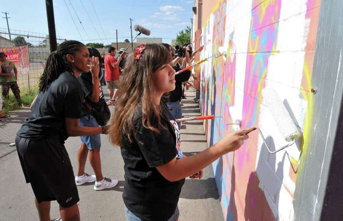 Kayla Gutierrez of the Guadalupe Cultural Arts Center's Team Up Challenge paints over graffiti at the back of the center with Silver Stars player Roneeka Hodges (left) on Wednesday, June 1, 2011. A mural called