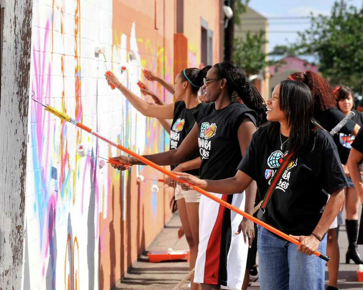 Silver Stars players Sophia Young (center) and Jia Perkins paint over graffiti at the Guadalupe Cultural Arts Center as part of a Team Up Challenge project. A mural called