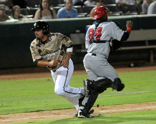 Arkansas Travelers' catcher Alberto Rosario (24) interferes with Missions runner Alis Solis during a rundown between third base and home plate at Wolff Stadium on Wednesday, June 1, 2011. Solis was awarded home on the play, scoring a run. Solis, a catcher, was one of eight Missions players selected for the 75th Texas League All-Star Game. Billy Calzada/gcalzada@express-news.net Photo: BILLY CALZADA, Express-News / gcalzada@express-news.net