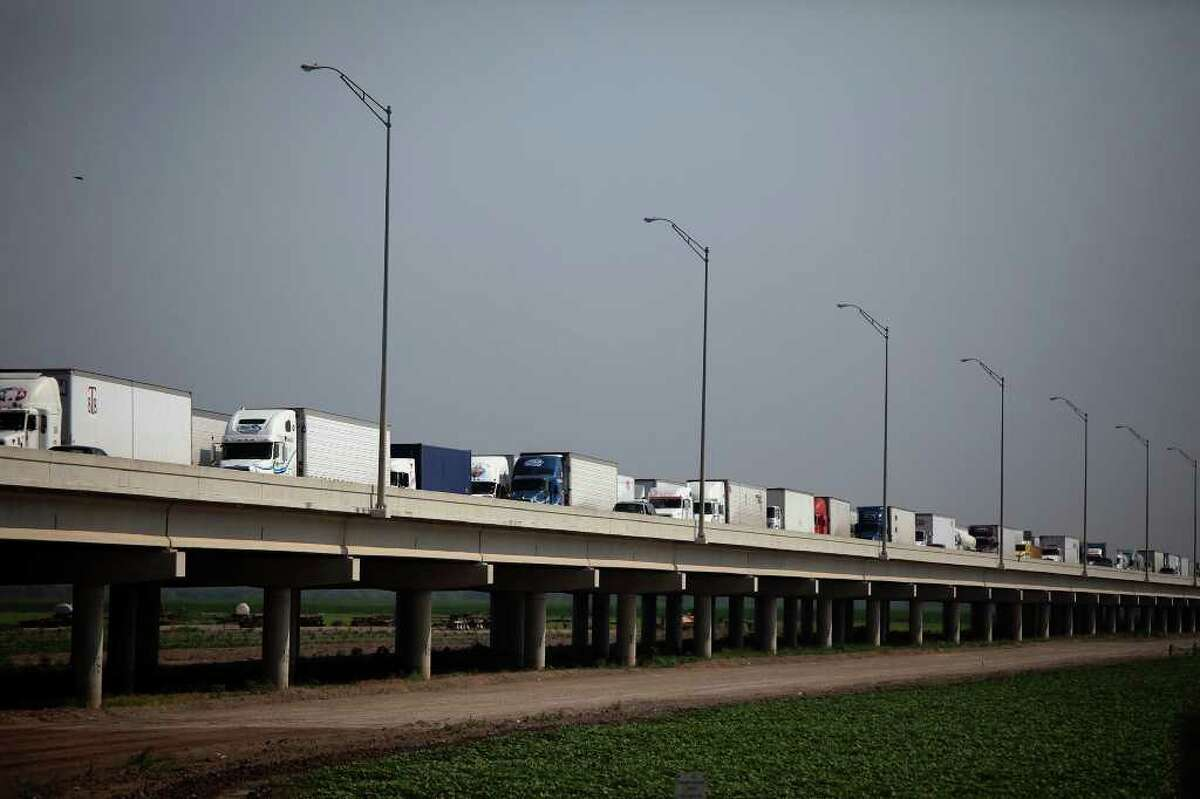 Trucks wait on the Pharr-Reynosa International Bridge to enter the U.S. In Pharr, customs officials inspect the cargo.