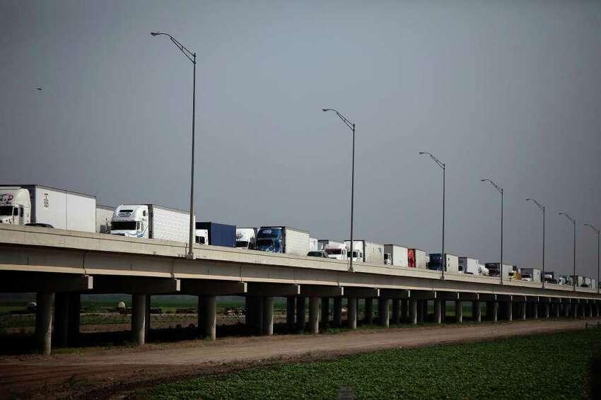 Trucks wait on the Pharr-Reynosa International Bridge to enter the U.S. In Pharr, customs officials inspect the cargo.