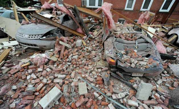 Bricks and debris that fell from a building lay on top of cars after a report of a tornado in Springfield, Mass., Wednesday, June 1, 2011. An apparent tornado struck downtown Springfield, one of Massachusetts' largest cities, scattering debris, toppling trees, and frightening workers and residents. (AP Photo/Jessica Hill) Photo: Jessica Hill