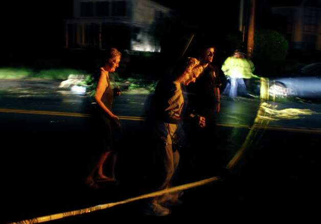 A police officer allows two residents to cross over caution tape on a devastated street after a tornado Wednesday swept through Monson, Mass. (Elise Amendola / Associated Press) Photo: Elise Amendola