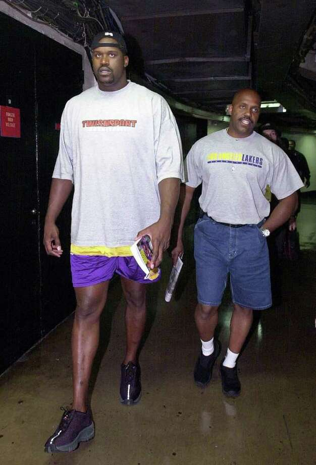 Los Angeles Lakers' Shaquille O'Neal, left, walks with bodyguard Jerome Crawford during practice, Monday, June 10, 2001, in Philadelphia. At 7-foot-1 and 330 pounds, O'Neal can take care of himself on the court. Elsewhere, he needs a little help. Photo: MARK J. TERRILL, AP / AP