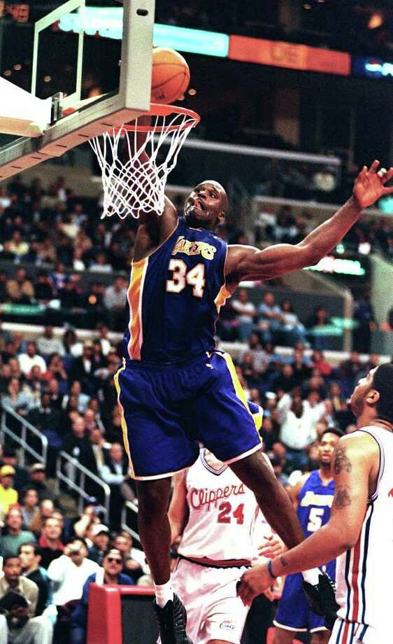 Los Angeles Lakers center Shaquille O'Neal dunks the ball during the game against the Los Angeles Clippers Monday, March 6, 2000.  In this season of campaigns, Shaquille O'Neal made a convincing pitch to MVP voters _ a career-high 61 points.   ``It's a good feeling,'' O'Neal said after the Los Angeles Lakers beat the Clippers 123-103 Monday night for their 16th consecutive victory, equaling their longest winning streak of the season. (AP Photo/E.J. Flynn). Photo: E.J. FLYNNN, AP / AP