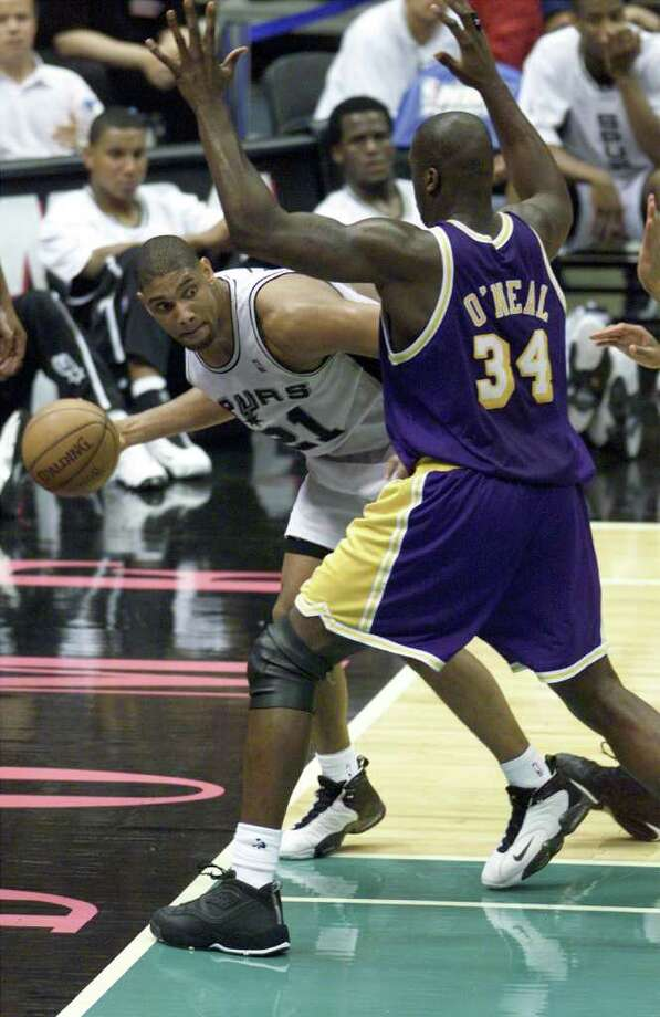 Spurs Tim Duncan tries to pass around the defense of Shaquille O'Neal.(JERRY LARA/STAFF