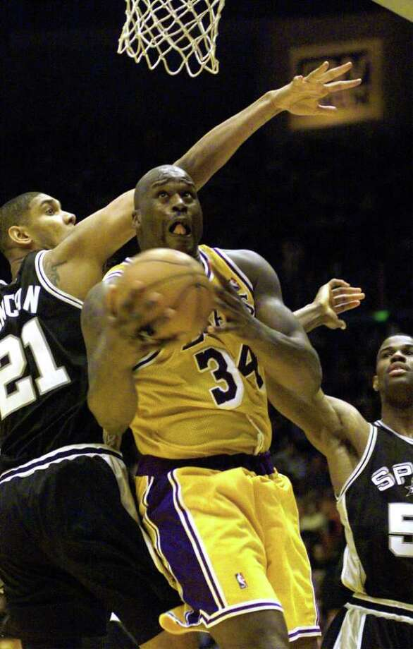 SPURS TIM DUNCAN DEFENDS AS SHAQUILE O'NEAL GOES TO THE HOOPS DURING THE SECOND HALF OF THE FOURTH GAME AT THE FORUM IN LOS ANGELES ON SUNDAY, MAY 23, 1999. JERRY LARA/STAFF