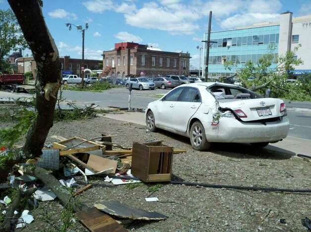 A car parked Thursday in Springfield, Mass., shows damage caused by tornadoes that hit the city the day before. (Dayeline Roman / Times Union)