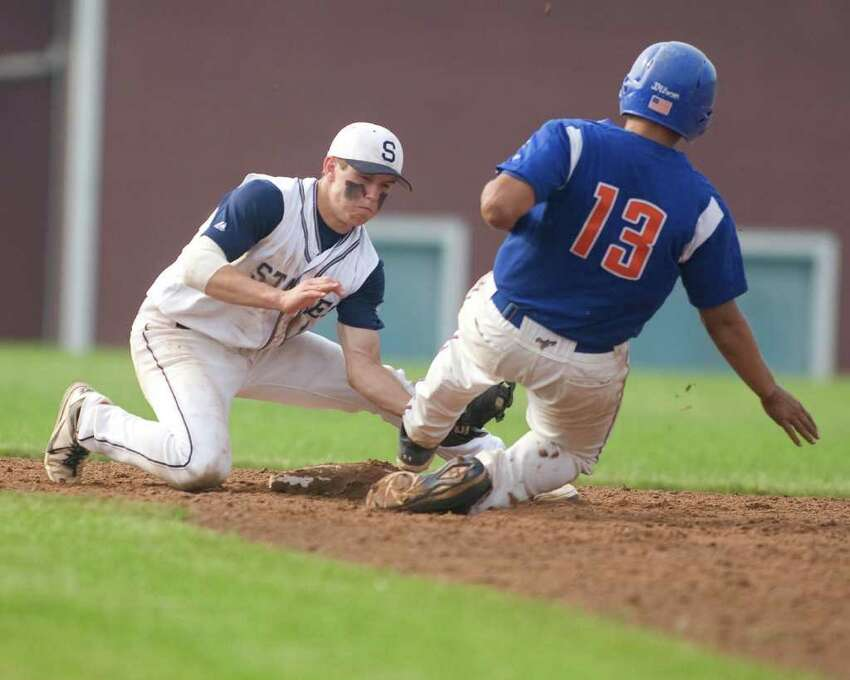 Staples' Mike Scott tags out Danbury's Garron Negron trying to steal during the Class LL state tournament second round game Wednesday at Danbury High School.
