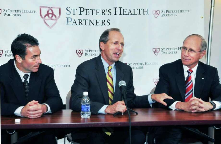 CEOs ,from left, Scott St. George of Seton Health, Steven Boyle of St. Peter?s Health Care Services and Dr. James Reed of Northeast Health unveil the new name and the new corporate logo for the health system created by their merger during a news conference in troy Thursday June 2, 2011.  (John Carl D'Annibale / Times Union) Photo: John Carl D'Annibale / 00013393A
