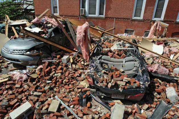 Vehicles were crushed by falling debris at an apartment building on Union Street after Wednesday's tornado tore the roof off the building in Springfield, Mass.  (Paul Buckowski / Times Union) Photo: Paul Buckowski
