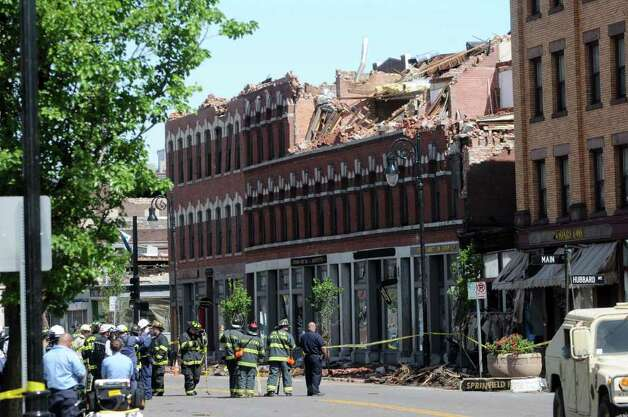 Firefighters gather Thursday to search buildings on Main Street after a tornado ripped through downtown Springfield, Mass., on Wednesday. (Paul Buckowski / Times Union) Photo: Paul Buckowski