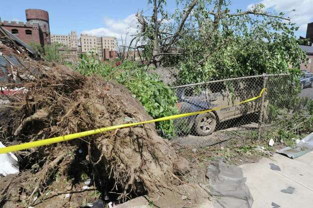 A car is crushed under a tree, seen here on Thursday morning June 2, 2011, after a tornado struck in downtown Springfield on Wednesday.  A portion of downtown Springfield sustained heavy damage from the storm that came through and fire and rescue crews were still searching buildings on Thursday morning.  (Paul Buckowski / Times Union) Photo: Paul Buckowski