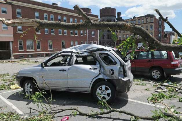 A car in a parking lot was was damaged by fallen trees after a tornado struck in downtown Springfield, Mass., on Wednesday.   (Paul Buckowski / Times Union) Photo: Paul Buckowski