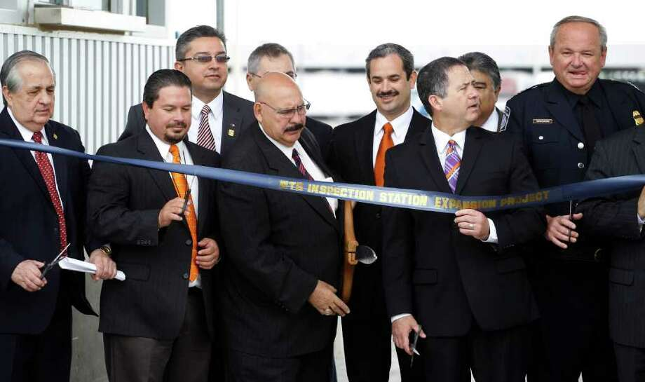 Dignitaries take part in a ribbon-cutting ceremony for the opening of seven new inspection booths for commercial traffic heading north into the U.S. from Mexico at the World Trade Bridge, Friday, May 6, 2011, in Laredo, Texas. The addition nearly doubles the capacity  of one of the busiest commercial bridges on America's southern border. Photo: Eric Gay, AP / AP
