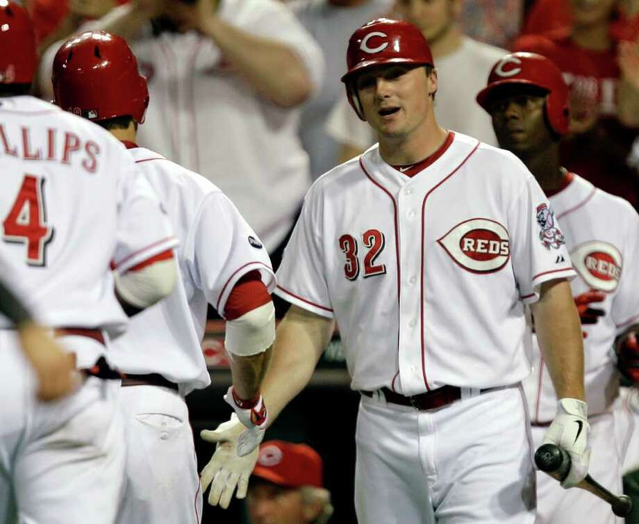 Cincinnati Reds' Jay Bruce (32) congratulates Joey Votto after Votto hit a two-run home run off Milwaukee Brewers relief pitcher Kameron Loe in the eighth inning of a baseball game, Wednesday, June 1, 2011, in Cincinnati. Bruce also had a two-run home run in the game won by Cincinnati 4-3. (AP Photo/Al Behrman) Photo: Al Behrman, STF / AP