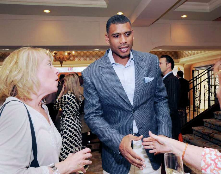At center, Allan Houston, former NBA All-Star and assistant general manager of the New York Knicks, shakes hands with Linda Bruno of Greenwich during the Greenwich Business Club Inc. benefit cocktail reception at The Delamar Greenwich Harbor Hotel, Thursday night, June 2, 2011.  At left is Laurinda Finelli of Greenwich. Photo: Bob Luckey / Greenwich Time