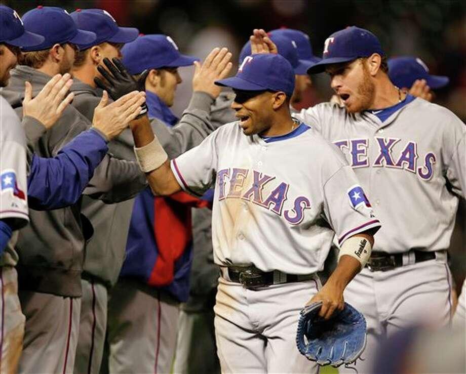 The Rangers' Endy Chavez (center) high-fives teammates after the Rangers beat the Indians 7-4 on Thursday. AMY SANCETTA ASSOCIATED PRESS / AP