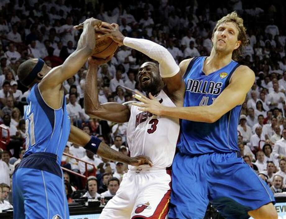 Dallas Mavericks' Dirk Nowitzki (41) and Jason Terry (31) defend Miami Heat's Dwyane Wade (3) during the second half of Game 2 of the NBA Finals basketball game Thursday, June 2, 2011, in Miami. (AP Photo/David J. Phillip) Photo: David J. Phillip, Associated Press / AP