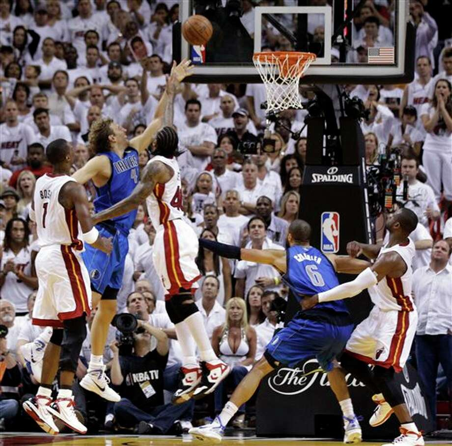 Dallas Mavericks' Dirk Nowitzki (41) aims at the basket as Miami Heat's Udonis Haslem and Chris Bosh (1) defend during the last minutes of the second half of Game 2 of the NBA Finals basketball game Thursday, June 2, 2011, in Miami. The Mavericks defeated the Heat 95-93.  (AP Photo/David J. Phillip) Photo: David J. Phillip, Associated Press / AP