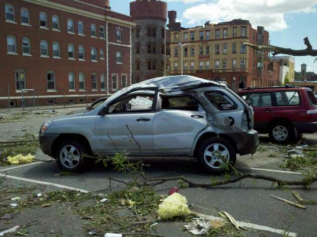 A car parked in Springfield, Mass., on Thursday, June 2, 2011, shows damage caused by tornadoes that hit the city the day before. (Dayeline Roman / Times Union)