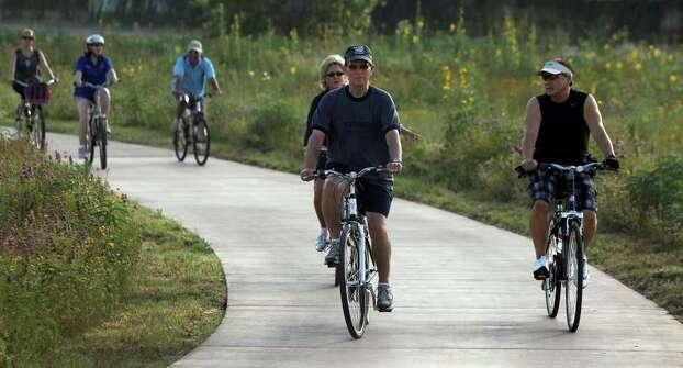 "Bexar County Judge Nelson Wolff (left front) and Bexar County Commissioner Sergio ""Chico"" Rodriguez (right front) lead the way on a cycling tour of the Mission Reach area of the San Antonio River on Thursday, June 2, 2011. The Mission Reach project should be completed by August 2013. Photo: John Davenport/Express-News"