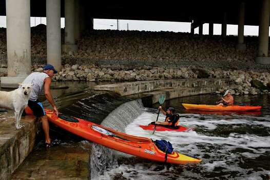 Tom Melee (left) carries his kayak over the dam with his dog, Wigger, while Craig Norris (center) plays in the currents created by the dam after dropping over it, next to Scott Rote (right), as they paddle on the Mission Reach portion of the San Antonio River to find out if it is accessible by canoe or kayak on Saturday, May 21, 2011. The San Antonio River Authority organized the trial run. Norris is the only one who was able to make it over the dam. Photo: Lisa Krantz/Express-News / SAN ANTONIO EXPRESS-NEWS