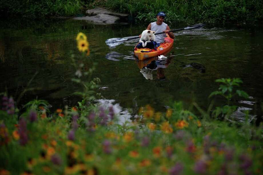 Tom Melee and his dog, Wigger, paddle on the Mission Reach portion of the San Antonio River to find out if it is accessible by canoe or kayak on Saturday, May 21, 2011. The San Antonio River Authority organized the trial run. Photo: Lisa Krantz/Express-News / SAN ANTONIO EXPRESS-NEWS