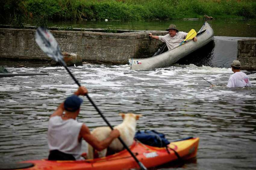 Kenneth Bennight maneuvers a small dam while Tom Melee and his dog, Wigger (left) and Randy Hohlaus (right) watch. The men were paddling on the Mission Reach portion of the San Antonio River on Saturday, May 21, 2011, to see if it is accessible by canoe or kayak. The San Antonio River Authority organized the trial run.
