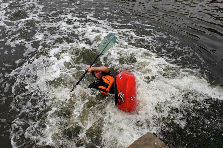 Craig Norris plays in the currents created by a chute on a small dam on the Mission Reach portion of the San Antonio River as he tries to find out if the river is accessible by canoe or kayak on Saturday, May 21, 2011. The San Antonio River Authority organized the trial run. Photo: Lisa Krantz/Express-News / SAN ANTONIO EXPRESS-NEWS