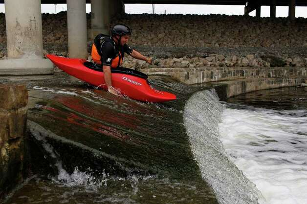 Craig Norris drops over a dam as he paddles on the Mission Reach portion of the San Antonio River to see if it is accessible by canoe or kayak on Saturday, May 21, 2011. The San Antonio River Authority organized the trial run. Photo: Lisa Krantz/Express-News / SAN ANTONIO EXPRESS-NEWS