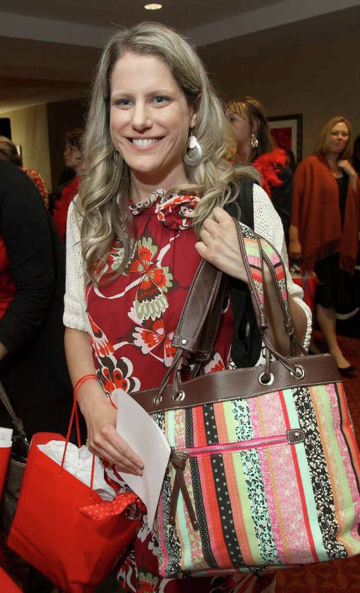 Erin Silk shows off the purse that she won from the silent auction during the 7th Annual Go Red For Women Luncheon on May 18, 2011, to benefit the American Heart Association. (Photo by Joe Putrock/Special to the Times Union)